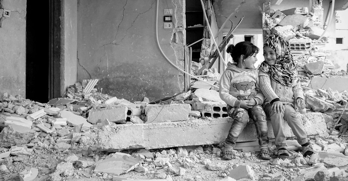 Crisis Action annual report 2017 cover - two girls in a bombed-out building in Syria